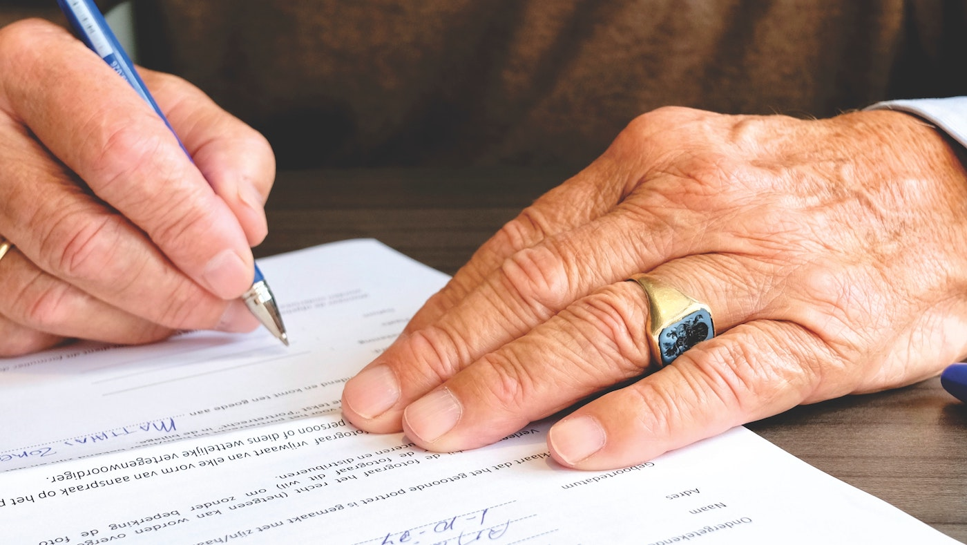 older man signing funeral papers